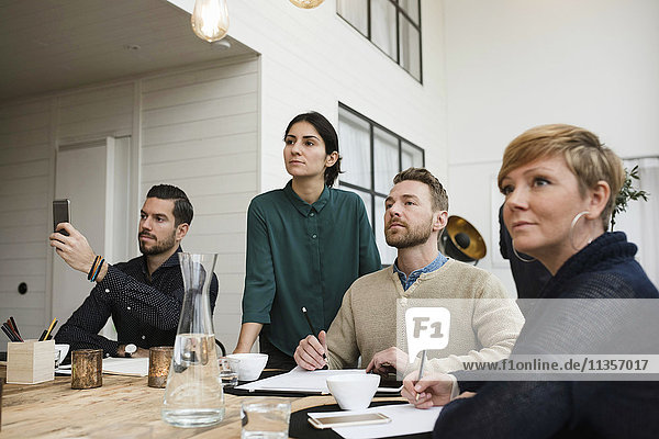 Geschäftsmann  der telefoniert  während er von Kollegen im Büro sitzt.