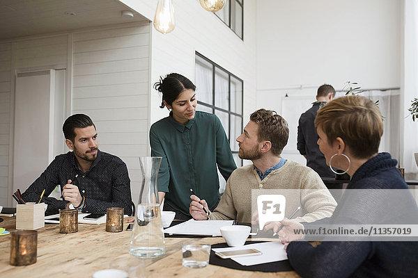 Mitarbeiter im Gespräch mit Geschäftsfrau am Tisch in der Besprechung