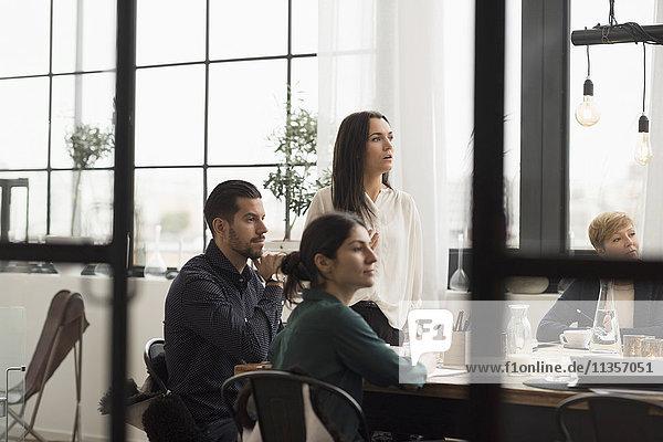 Geschäftsmann und Geschäftsfrau  die während der Besprechung im Büro zuhören.
