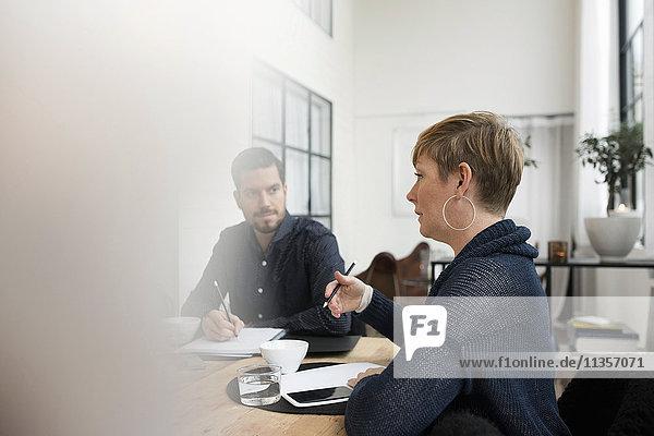 Business-Profi im Gespräch mit Kollegen während des Meetings am Tisch