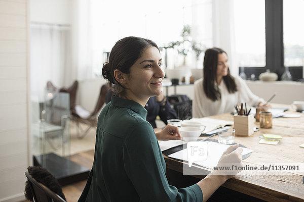 Lächelnde Geschäftsfrau sitzend mit Kollegen am Tisch im Meeting