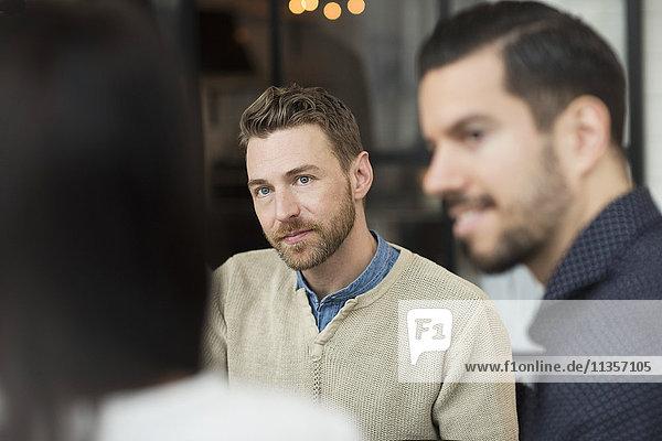 Geschäftsleute  die eine Frau während einer Besprechung im Büro anschauen