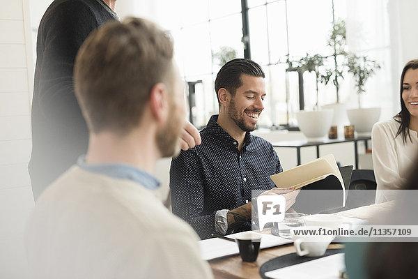 Glücklicher Geschäftsmann liest Dokument  während er mit Kollegen am Tisch im Büro sitzt.