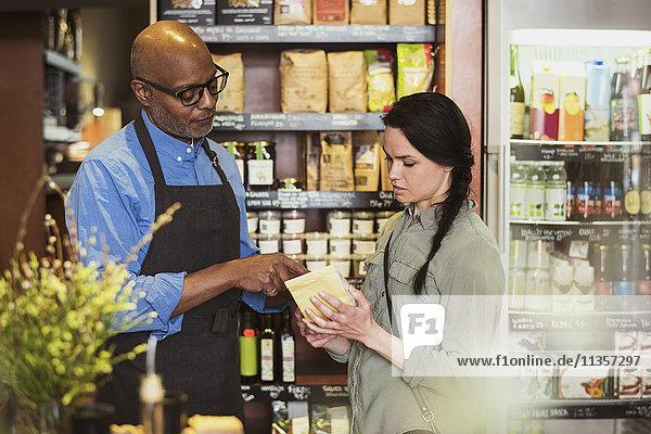 Besitzer und Kunde besprechen über Paket im Geschäft