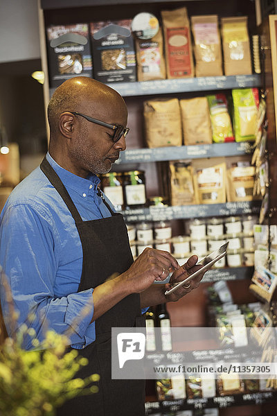 Seitenansicht des Seniorbesitzers mit digitalem Tablett im Geschäft