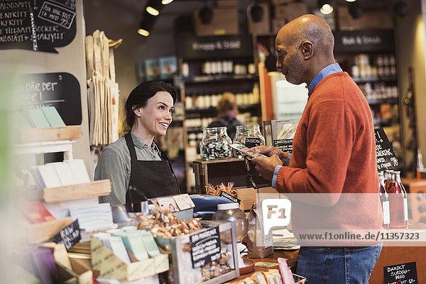 Lächelnder Besitzer im Gespräch mit dem Kunden  der das Paket hält  während er im Geschäft steht.