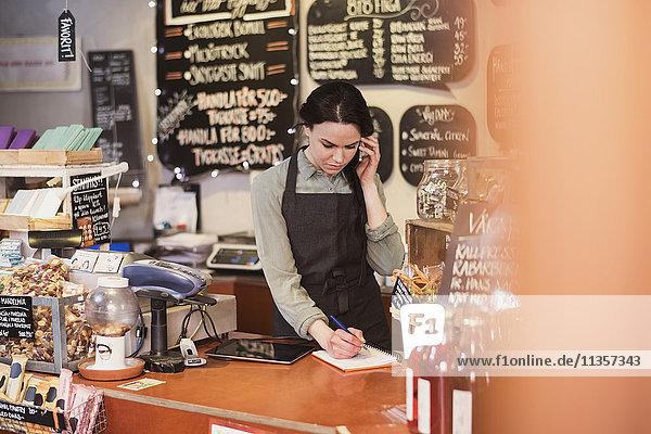 Der Besitzer spricht am Telefon  während er auf den Notizblock an der Kasse im Geschäft schreibt.