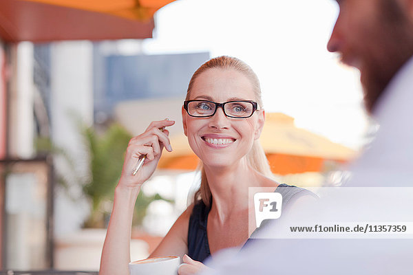 Mature man and woman  sitting outside cafe  having discussion
