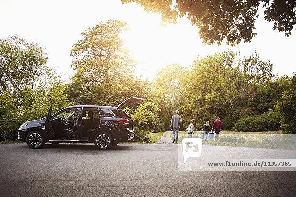 Offenes schwarzes Elektroauto mit Familienwanderung im Park