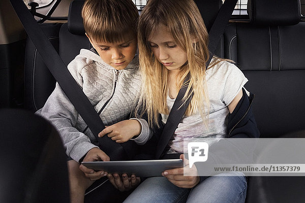 Geschwister mit digitalem Tablett im Sitzen im Elektroauto