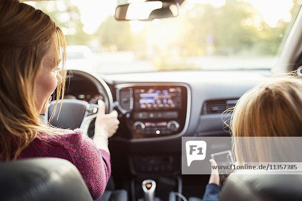 Rückansicht der Frau und des Mädchens im Elektroauto