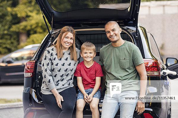 Porträt einer glücklichen Familie  die im Kofferraum im Hinterhof sitzt.