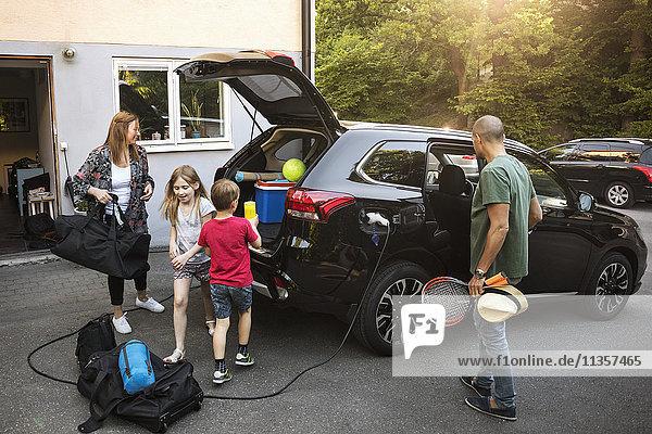 Familie mit Gepäck und schwarzem Elektroauto im Hinterhof