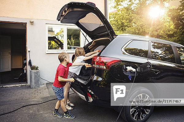 Kinder laden schwarzen Elektroauto Kofferraum gegen Haus im Hinterhof