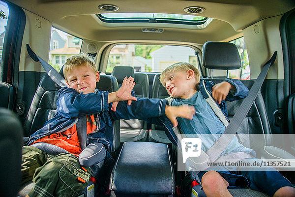 Zwillingsbrüder sitzen hinten im Fahrzeug und kämpfen