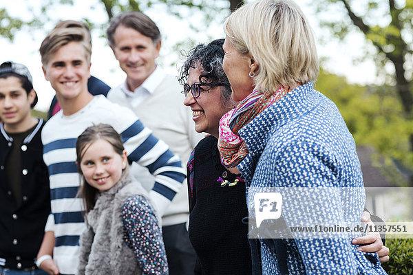 Lächelnde reife Frau mit Familie und Freunden im Hof