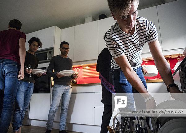 Blick auf den Teenager  der nach dem Abendessen Teller in der Geschirrspülmaschine anordnet.