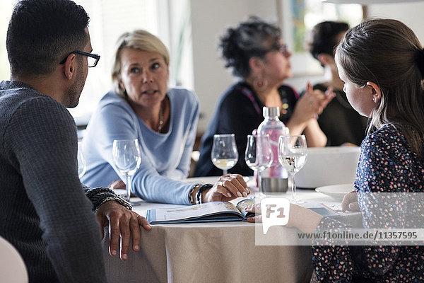 Mutter im Gespräch mit Tochter und Mann mit Magazin auf der Dinnerparty