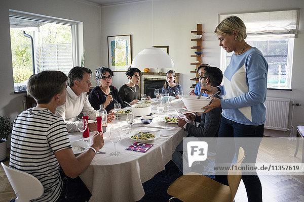Frau serviert Essen für Familie und Freunde am Esstisch in der Dinnerparty