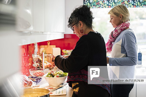 Multiethnische Freunde bereiten Salat in der Küche zu Hause zu.