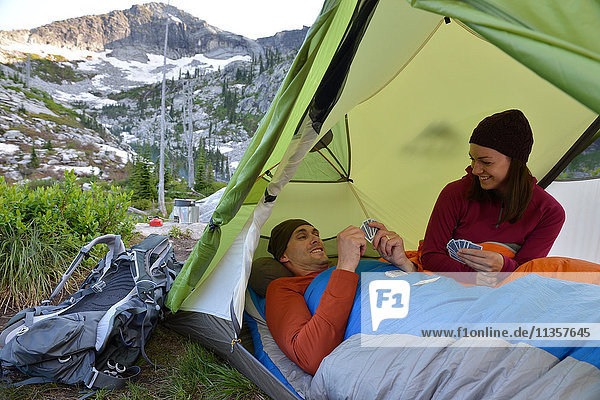 Couple playing card game in tent at Fault Lake  Selkirk Mountains  Idaho
