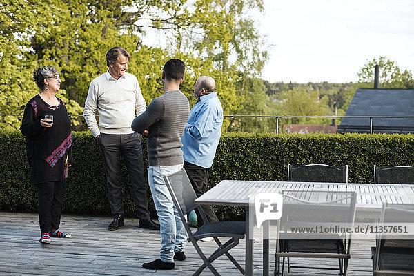 Multi-ethnische Freunde beim Reden am Tisch im Hof