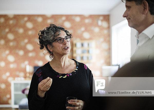 Frau mit Trink-Gesten im Gespräch mit dem Mann zu Hause