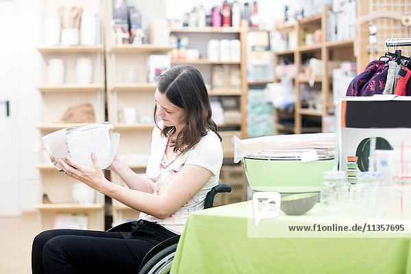 Young woman using wheelchair browsing in shop