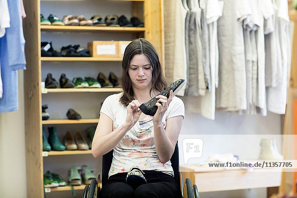 Young woman using wheelchair looking at shoes in shop