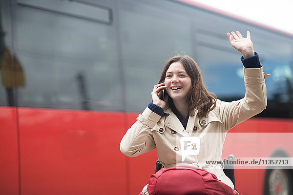 Young woman using wheelchair waving from city bus station