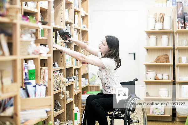 Young female shop assistant using wheelchair tidying up shop shelves