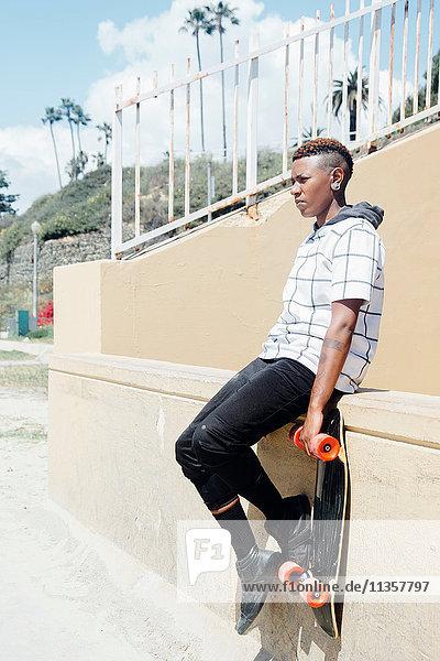 Frau sitzt an der Wand und hält Skateboard und schaut weg