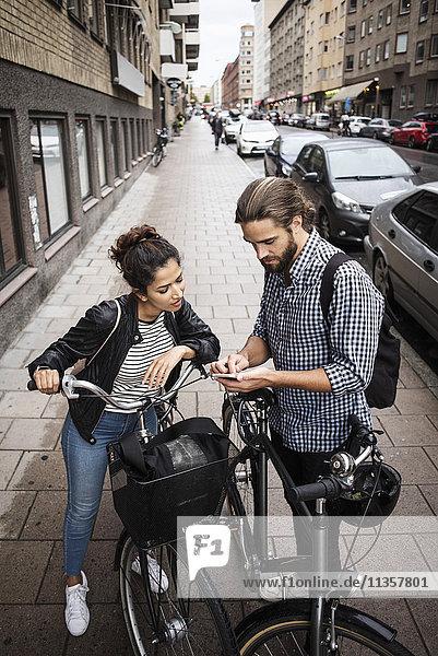 Hochwinkelansicht von Freunden mit Fahrrädern  die auf dem Bürgersteig in der Stadt stehen und das Telefon anschauen