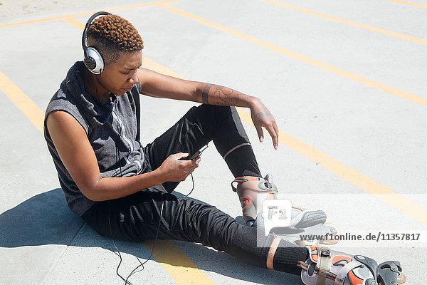 Woman wearing rollerblades and headphones sitting on floor looking at smartphone