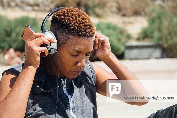 Frau mit Kopfhörern hält Smartphone in der Hand und schaut nach unten