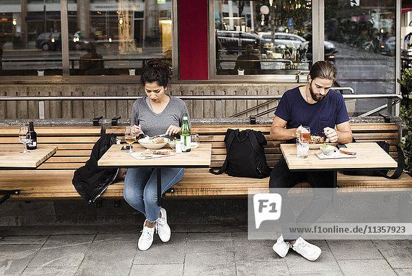 Volle Länge des Mannes und der Frau  die Nahrung am Bürgersteigcafe haben