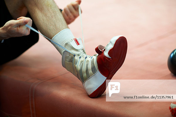 Boxer tying shoelace  low section