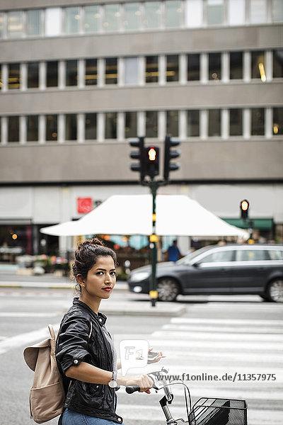 Porträt einer Frau mit Fahrrad  die ein Handy hält  während sie auf der Straße steht.