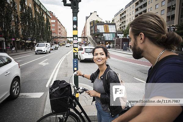 Lächelnde Frau mit Fahrrad  die einen Freund ansieht  während sie mitten in der Stadt steht.