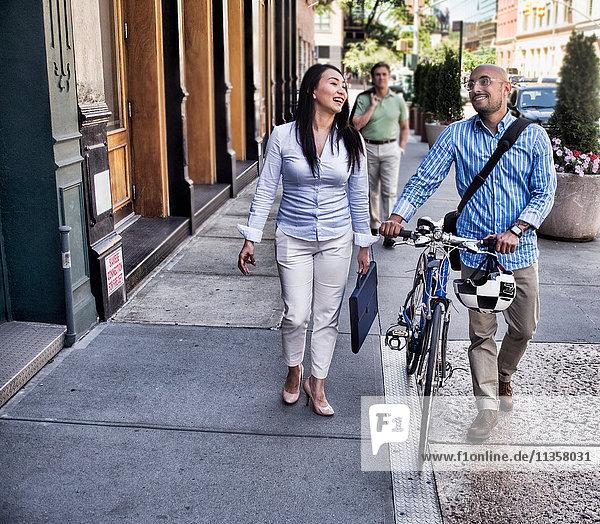 Business man and woman walking in street  man pushing bike  smiling