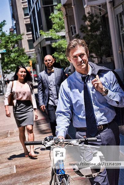 Geschäftsleute gehen auf der Straße  reifer Mann schiebt Fahrrad