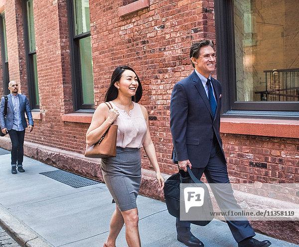 Geschäftsmann und -frau gehen gemeinsam lächelnd auf der Straße