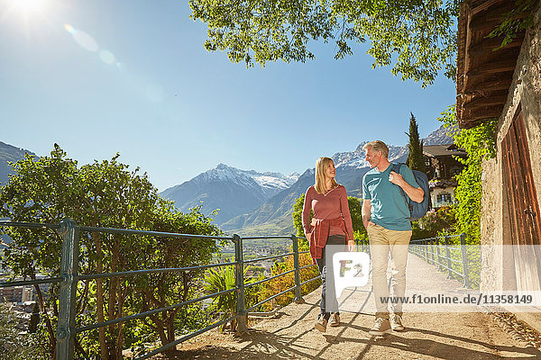 Mature couple hiking along country road  Meran  South Tyrol  Italy