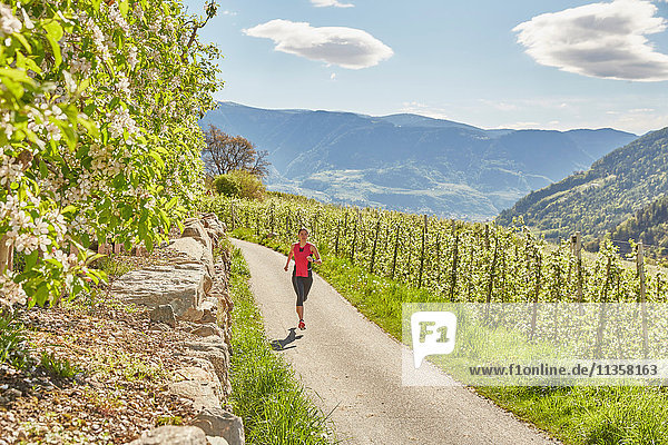 Junge Frau läuft entlang einer Landstraße  Meran  Südtirol  Italien