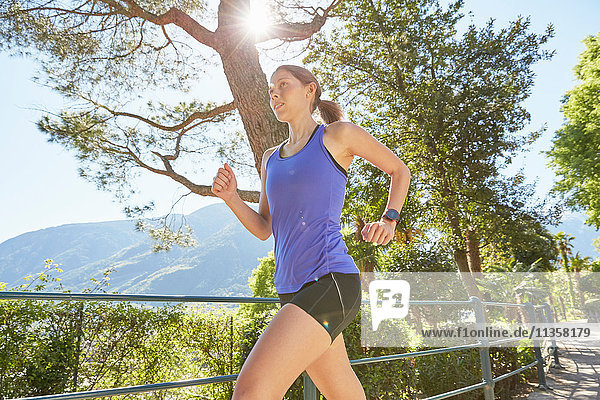 Young woman running along rural pathway  Meran  South Tyrol  Italy
