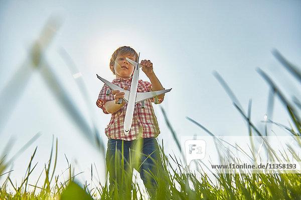 Niedrigwinkel-Ansicht eines Jungen  der im Gras steht und das Heck eines Spielzeugflugzeugs kontrolliert
