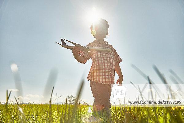 Junge auf sonnenbeschienenem Feld spielt mit Spielzeugflugzeug