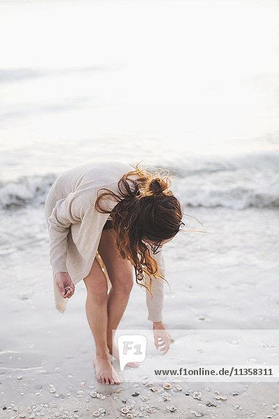 Woman picking seashells on beach