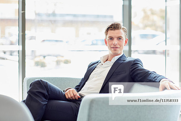 Portrait of young male businessman on office sofa