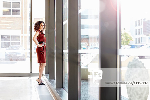 Confident young businesswoman looking out at office window